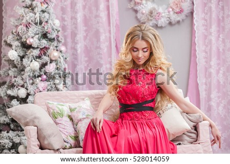 Beautiful young girl with long wavy hair in a pink dress on a background of the Christmas tree. Christmas and New Year in the picture.