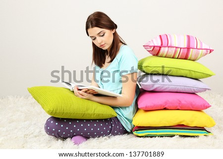 Beautiful young girl with pillows and book in room