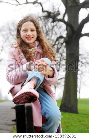 Beautiful young girl with red curly hair relaxing and sitting down on a wooden bench in a park during a cold winter day, wearing a pink coat and a scarf, smiling outdoors. - stock photo