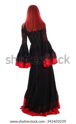 Beautiful young girl with red hair, wearing a long  gothic black and red flamenco lace gown with black corset. standing back view, isolated on white background.  - stock photo