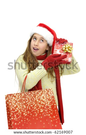 Beautiful young girl with santa's hat and shopping bags isolated in white