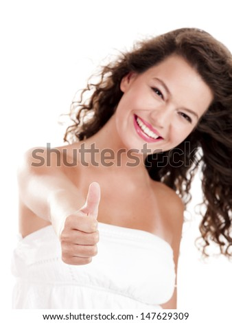 Beautiful young girl with thumbs up isolated on white, focus is on the hand - stock photo