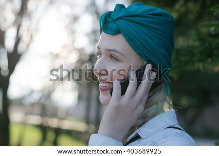 Beautiful young girl with turban using phone