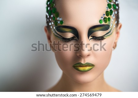 Beautiful young girl, woman, lady, predator, dragon, witch, alien, fairytale. Mythical, stylish look. Bright creative makeup, perfect skin, expressive eyes, color yellow, green, gems, crystals, strass - stock photo