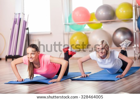 Beautiful young girls are doing press-up in gym. They are smiling and looking forward with joy - stock photo