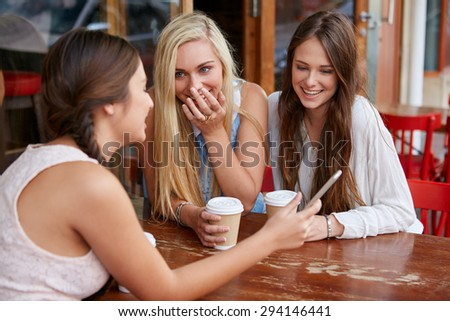 beautiful young girls having coffee at outdoor cafe with mobile cell phone - stock photo