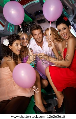 Beautiful young girls having party fun in limousine with handsome man. - stock photo