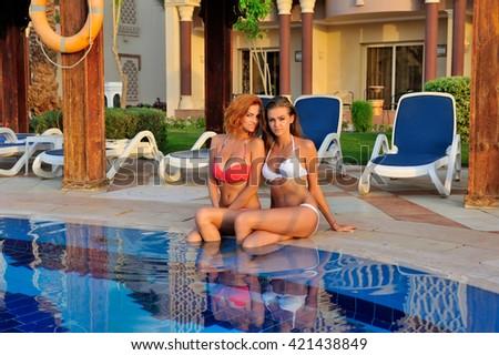 Beautiful young girls in bikini resting by the pool - stock photo