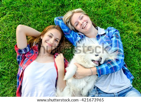 beautiful young girls playing with her dog outdoor - stock photo