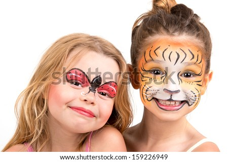 Beautiful young girls with painted faces, tiger and ladybug - stock photo
