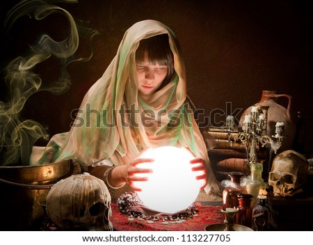 Beautiful young gypsy reading the future in a crystral ball - stock photo