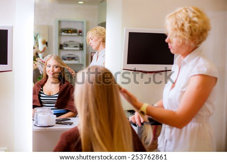 Beautiful young hairdresser giving a new haircut to female customer at parlor - stock photo