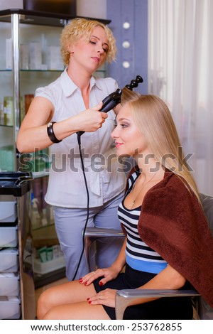 Beautiful young hairdresser giving a new haircut to female customer at parlor, hair care - stock photo