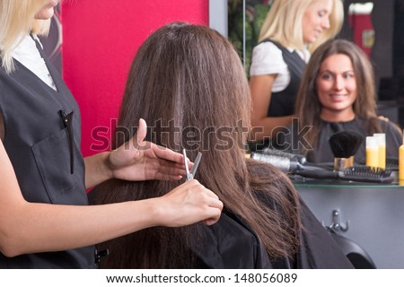 beautiful young hairdresser giving a new haircut to female customer in beauty salon - stock photo