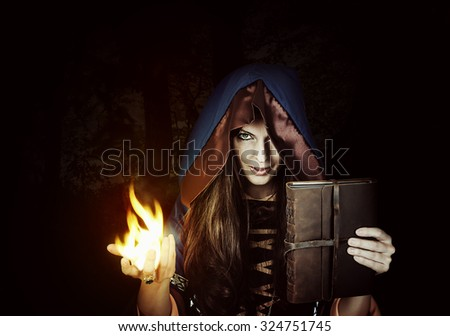 Beautiful young halloween witch - fire wizard wearing vintage gothic dress with hood holding magical book of spells in old leather cover in dark night forest