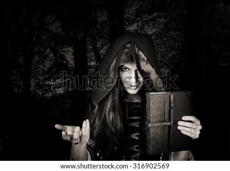 Beautiful young halloween witch wearing vintage gothic dress with hood holding magical book of spells in old leather cover in dark night forest