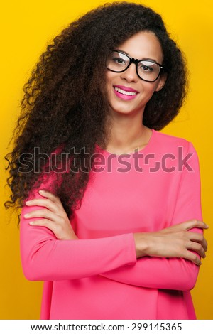 Beautiful young happy african american woman with amazing toothy smile. Girl looking at camera, wearing eyeglasses. Girl with long healthy curly hair. Studio shot.  - stock photo