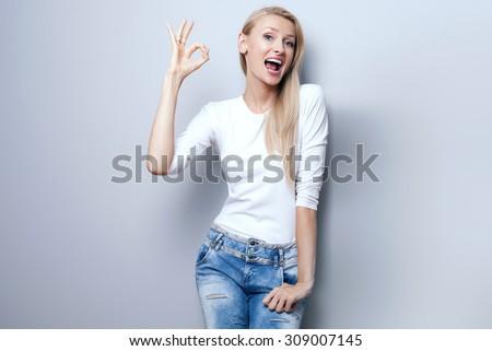 Beautiful young happy blonde girl posing, smiling, looking at camera. Studio shot. Happy woman. - stock photo