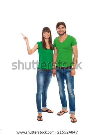 beautiful young happy couple love smiling embracing point finger to empty copy space, man and woman smile wear green t shirt jeacns full length portrait, isolated over white background