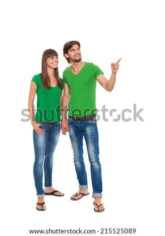 beautiful young happy couple love smiling embracing point finger to empty copy space, man and woman smile wear green t shirt jeacns full length portrait, isolated over white background - stock photo