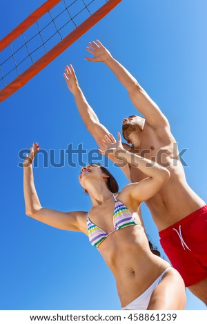 Beautiful  young happy couple  playing volleyball on the beach - stock photo