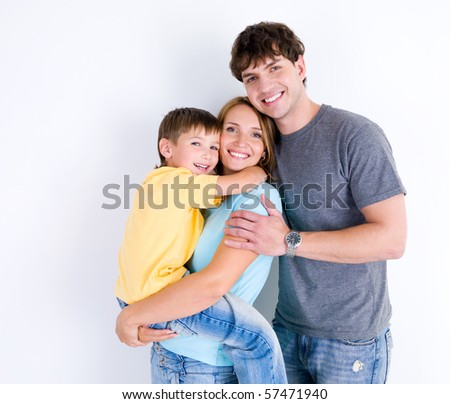 Beautiful young happy family in embrace with little son - indoors