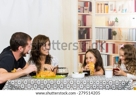 Beautiful young happy family with two cute girls eating meal  - stock photo