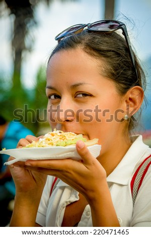 beautiful young happy girl eating a tostada soft taco pupusas in guatemala - stock photo