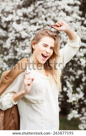 Beautiful young happy girl in blossom garden on a spring day - stock photo