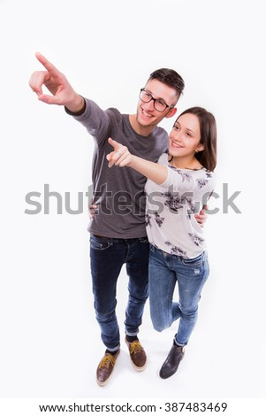 beautiful young happy hipster couple love smiling embracing point finger to empty copy space, man and woman smile looking up, isolated over white background