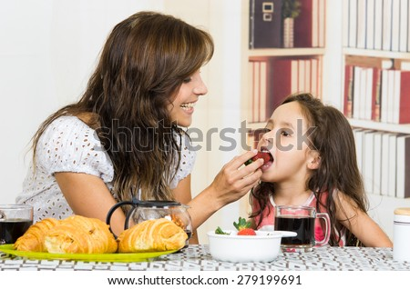Beautiful young happy mom feeding fruit to cute little girl - stock photo