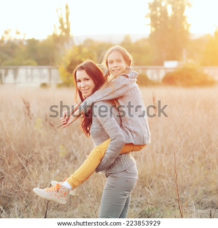 Beautiful young happy mother with little girl on the back. Closeup of a happy family on a walk in a field in the sunshine. Photo toned style Instagram filters. - stock photo