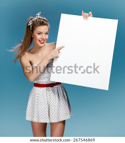 Beautiful young happy smile woman standing hold blank board / photo set of young American pin-up model on blue background with space for text - stock photo