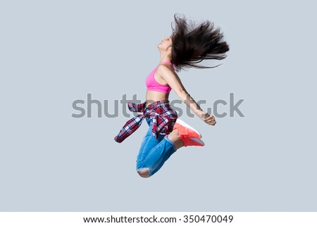 Beautiful young happy smiling fit modern hip-hop dancer woman working out wearing jeans, jumping, studio, gray background, full length - stock photo