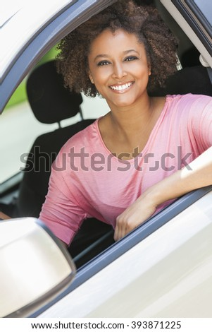 Beautiful young happy smiling mixed race black African American woman driving a car - stock photo