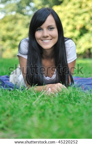 Beautiful young happy smiling woman lying in grass outdoors with copy space