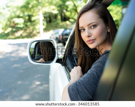 Beautiful young happy woman in car. Attractive  caucasian girl sitting in white auto. pretty female person driving big car suv - stock photo
