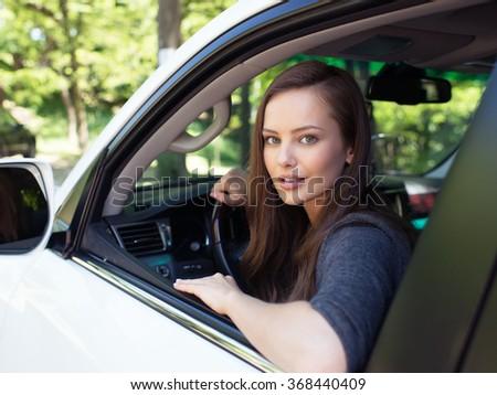 Beautiful young happy woman in car. Attractive  smiling caucasian girl sitting in white auto. pretty female person driving big car suv - stock photo