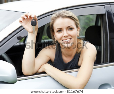 Beautiful young happy woman in car showing the keys - stock photo