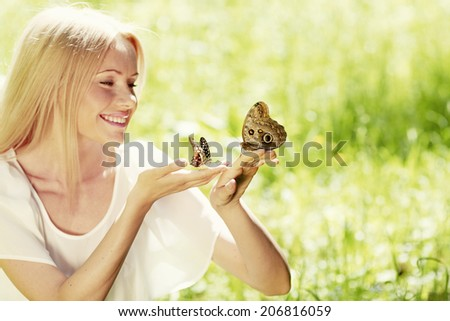 Beautiful young happy Woman playing with butterfly outdoors - stock photo
