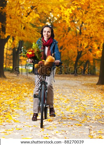 Beautiful young happy woman riding a bycicle in an autumn park