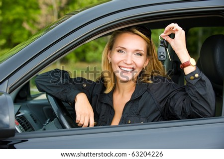 Beautiful young happy woman shows keys from the new car - outdoors - stock photo