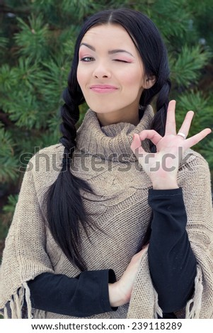 beautiful young happy woman winks and shows like OK in the forest near trees winter day - stock photo