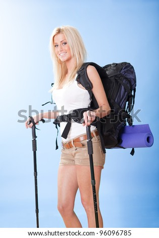 Beautiful young hiking woman with backpack and jogging sticks - stock photo