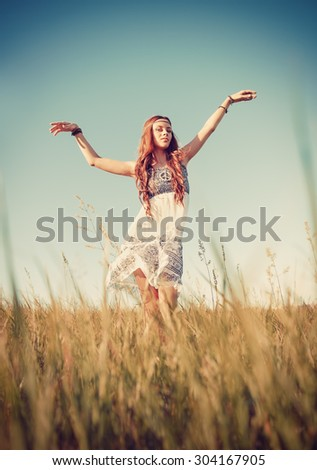 Beautiful young hippie girl dancing in the field. Sunset time - stock photo