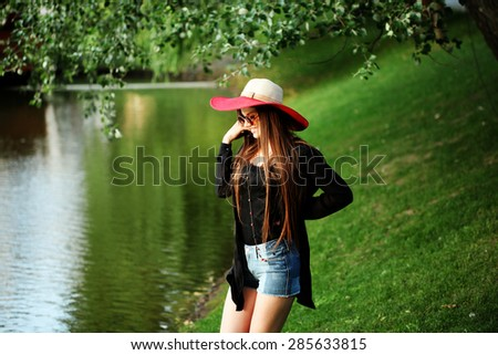 Beautiful young hippie girl outdoors enjoying nature. Trendy boho fashion Caucasian woman wearing black cardigan, hat and denim jeans. - stock photo
