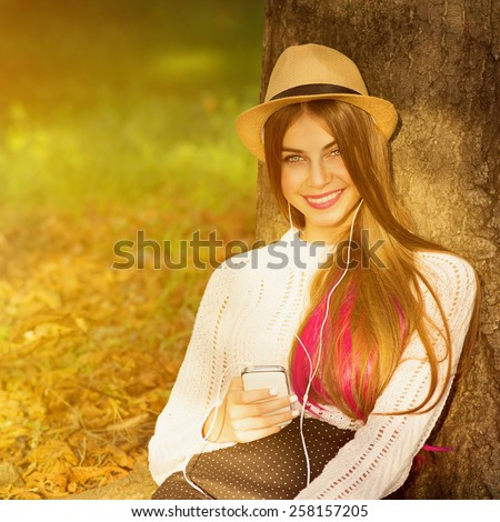 Beautiful young hipster Caucasian woman with smartphone and earphones in park sitting, texting and listening to music. Happy teenage girl with long blonde and pink hair wearing boho outfit. Retouched. - stock photo
