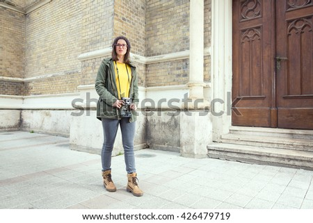 Beautiful young hipster girl holding an old-fashion camera while walking down the street of an old European town - stock photo