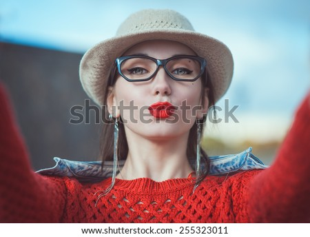 Beautiful young hipster girl in the hat and glasses taking picture of herself, selfie outdoor - stock photo