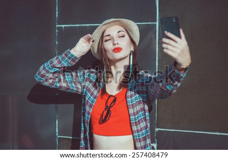 Beautiful young hipster girl in the hat taking picture of herself, selfie near wall - stock photo